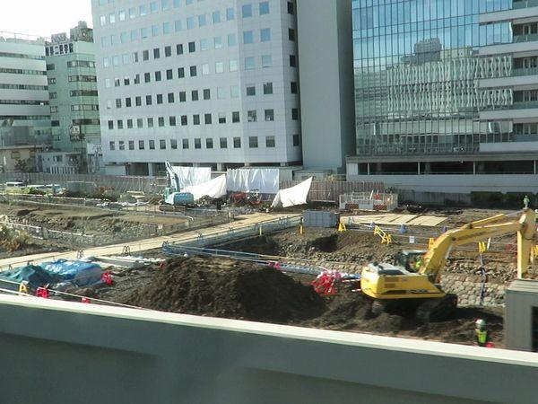 京浜東北線高輪ゲートウェイ→田町の車窓から見た車両基地跡地の再開発エリア。右下の重機の後ろに高輪築堤の石垣が見える。
